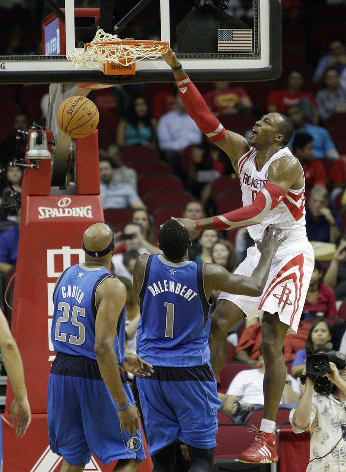 Houston Rocket's Dwight Howard, right, dunks over Dallas Maverick's Vince Carter, left,  and Dallas Maverick's  Samuel Dalembert, center, in the first half of a preseason NBA basketball game Monday, Oct. 21, 2013, in Houston. (AP Photo/Bob Levey)