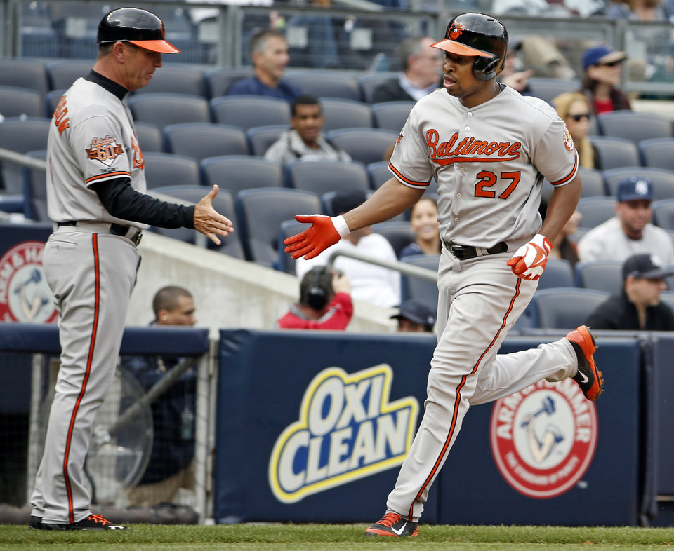 Photo - Baltimore Orioles third base coach Bobby Dickerson congratulates Delmon Young, right, after Young's sixth-inning, two-run home run off New York Yankees starting pitcher Vidal Nuno in a baseball game at Yankee Stadium in New York, Tuesday, April 8, 2014.  (AP Photo/Kathy Willens)