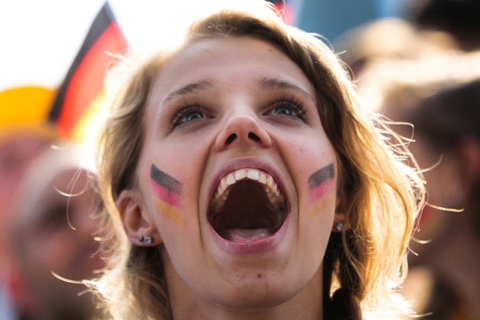 Photo - A German soccer fan celebrates their team's third goal during their first game at the World Cup 2014 at a public viewing zone called 'fan mile' in Berlin, Monday, June 16, 2014. Germany plays against Portugal in group G match at the soccer World Cup 2014 in Brazil. (AP Photo/Markus Schreiber)
