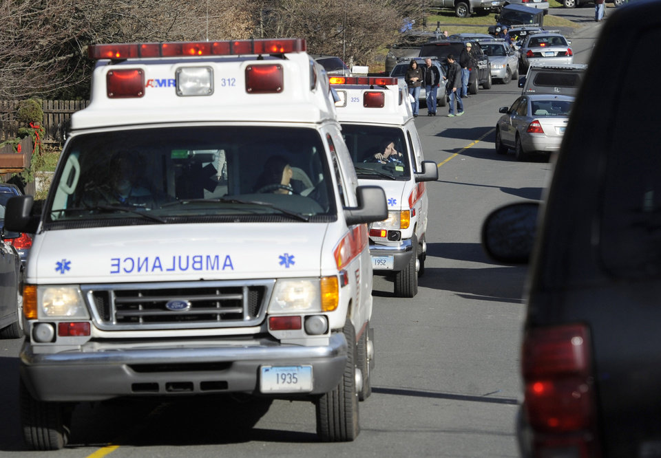 Photo - Ambulances leave an area near the scene of a shooting at Sandy Hook Elementary School in Newtown, Conn. where authorities say a gunman opened fire, leaving 27 people dead, including 20 children, Friday, Dec. 14, 2012. (AP Photo/Jessica Hill) ORG XMIT: CTJH110