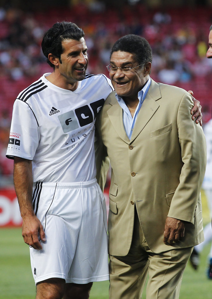 Photo - FILE - In this July 18, 2012 file photo, Eusebio embraces Portuguese star player Luis Figo, left, prior to 'An Act Against Hunger' friendly soccer match between Benfica and Luis Figo and the Rest of the World team at Benfica's Luz stadium in Lisbon. Eusebio, the Portuguese football star who was born into poverty in Africa but became an international sporting icon and was voted one of the 10 best players of all time, has died of heart failure aged 71, Sunday, Jan. 5 2014. (AP Photo/Francisco Seco, File)