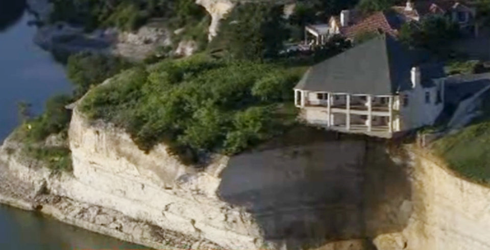 Photo - In this image taken from Tuesday, June 10, 2014 video provided by WFAA-TV, a luxury house teeters on a cliff about 75 feet above Lake Whitney in Whitney, Texas. WFAA-TV reported Wednesday, June 11, 2014 that the house has been condemned and the owners evacuated about two weeks ago. (AP Photo/WFAA.com)