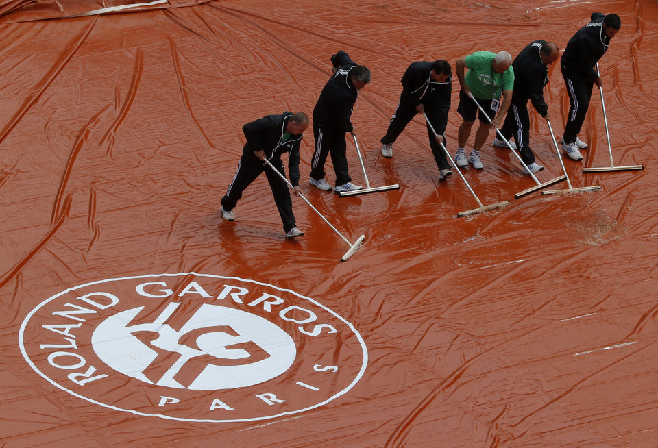 Photo - Stadium employees wipe the protective canvas on center court after rain delayed the play for the first round match of  the French Open tennis tournament at the Roland Garros stadium, in Paris, France, Monday, May 26, 2014. (AP Photo/Michel Euler)