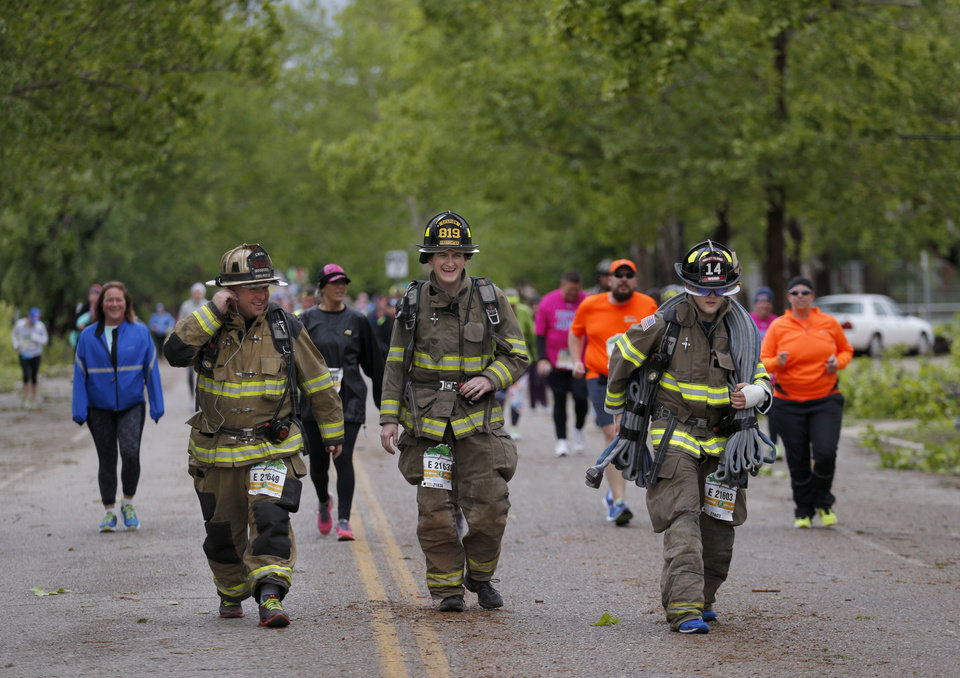 Photo - Fire fighters walk near N. Robinson Ave and NW 28th St. during the 2017 Oklahoma City Memorial Marathon Sunday, April 30, 2017.  Photo by Sarah Phipps, The Oklahoman