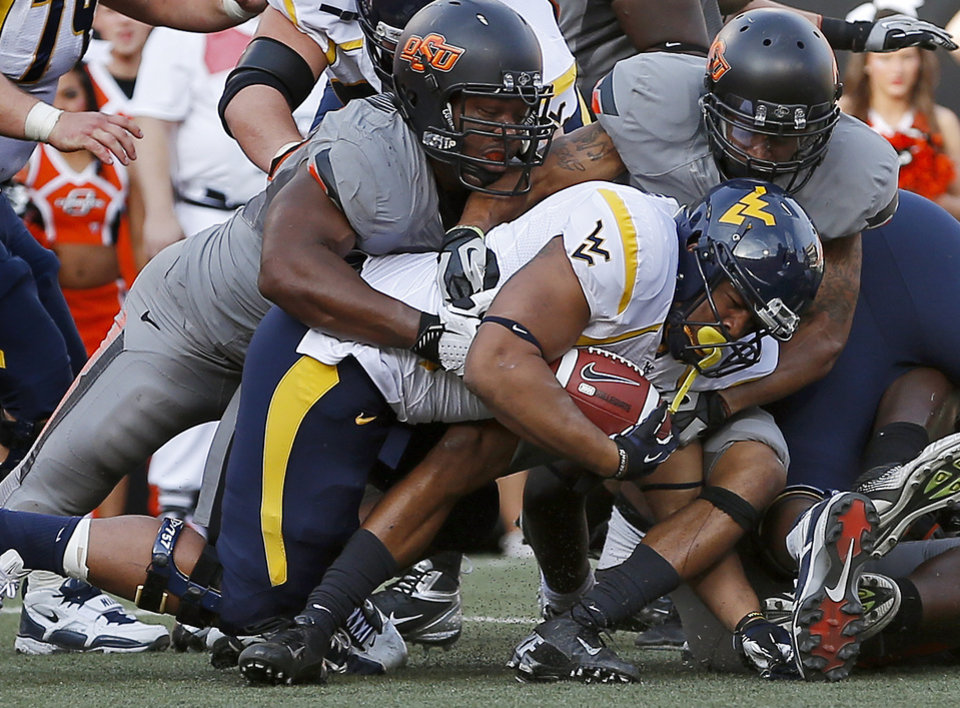 Photo - Oklahoma State's Tyler Johnson, left, and Shamiel Gary bring down West Virginia's Shawne Alston on a fourth down play  during a college football game between Oklahoma State University (OSU) and West Virginia University at Boone Pickens Stadium in Stillwater, Okla., Saturday, Nov. 10, 2012. Oklahoma State won 55-34. Photo by Bryan Terry, The Oklahoman
