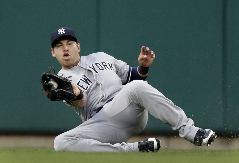 Photo - New York Yankees center fielder Jacoby Ellsbury slides and catches a ball hit by St. Louis Cardinals' Allen Craig for an out during the second inning of a baseball game Wednesday, May 28, 2014, in St. Louis. (AP Photo/Jeff Roberson)