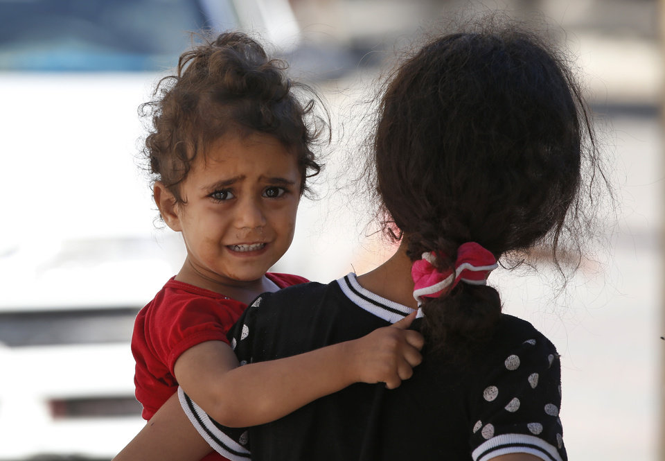 Photo - A girl cries as Palestinians flee their homes in the Shajaiyeh neighborhood of Gaza City, after Israel had airdropped leaflets warning people to leave the area, Wednesday, July 16, 2014. Palestinians flee their home in Gaza City, Wednesday, July 16, 2014. Alongside the air strikes, Israel also ordered tens of thousands of residents of the northern town of Beit Lahiya and the Zeitoun and Shijaiyah neighborhoods of Gaza City, all near the border with Israel, to evacuate their homes by 8 A.M. Wednesday. The warnings were delivered in automated phone calls, text messages and leaflets. (AP Photo/Lefteris Pitarakis)