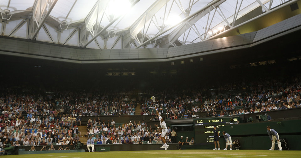 Photo - Novak Djokovic of Serbia serves to Jo-Wilfried Tsonga of France during their men's singles match at the All England Lawn Tennis Championships in Wimbledon, London, Monday, June 30, 2014. The match is being played on Centre Court under the roof due to the weather.(AP Photo/Pavel Golovkin)