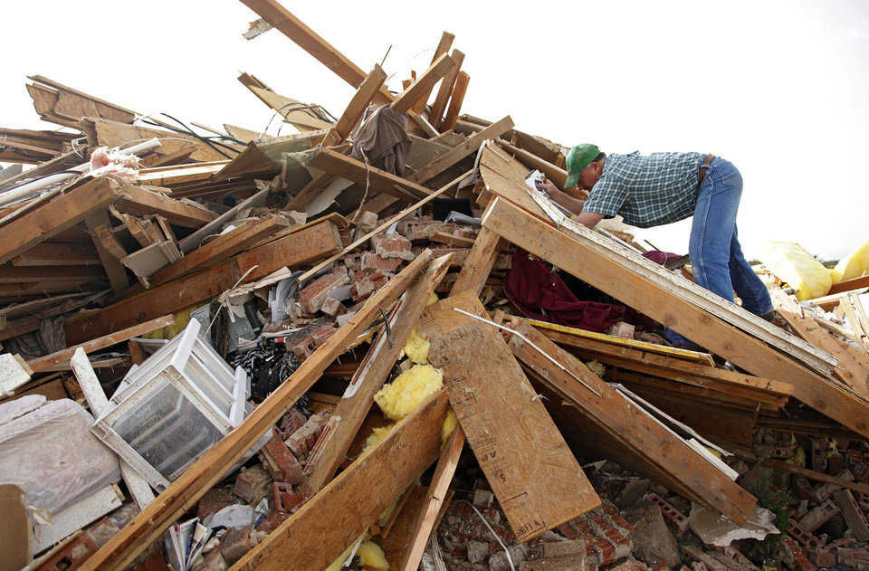 A neighbor pitches in to help recover items out of the home of Scott and M'Lynn McCann's home that was destroyed by a tornado west of El Reno, Tuesday, May 24, 2011. Photo by Chris Landsberger, The Oklahoman ORG XMIT: KOD