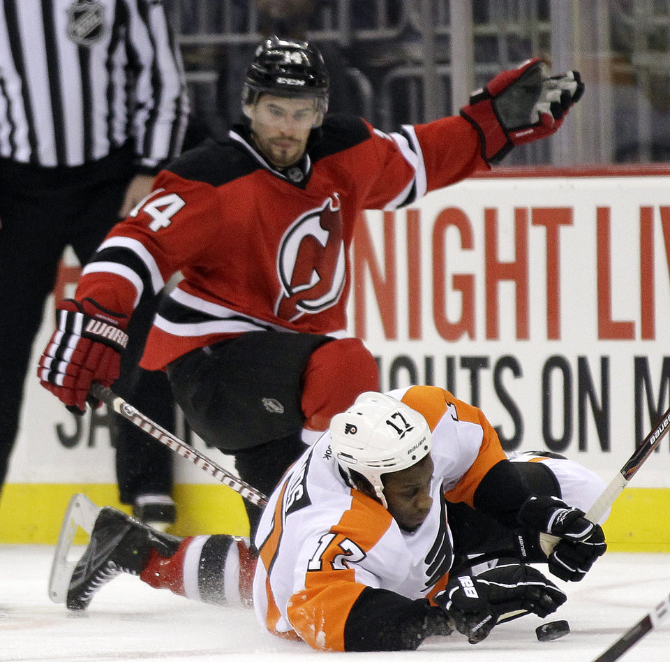 Philadelphia Flyers' Wayne Simmonds, bottom and New Jersey Devils' Adam Henrique compete for the puck in the first period of Game 3 of a second-round NHL hockey Stanley Cup playoff series, Thursday, May 3, 2012 in Newark, N.J. (AP Photo/Julio Cortez)