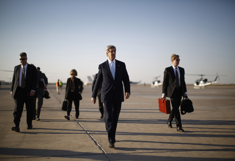 Photo - U.S. Secretary of State John Kerry, second right, walks across the tarmac of Baghdad International Airport as he prepares to board an aircraft out of the Iraqi capital Sunday, March 24, 2013. Kerry was in Iraq today, meeting with officials in an unannounced visit. He says he made it clear in talks with the Iraqi Prime Minister Nouri al-Maliki that the U.S. is unhappy with Iraq for letting Iran use its airspace to ship weapons and fighters to Syria. (AP Photo/Jason Reed, Pool)