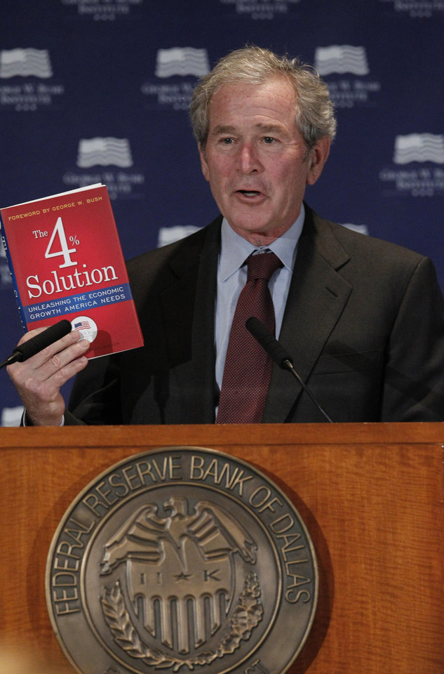 Photo - Former President George W. Bush holds up a book as he gives opening remarks at the Federal Reserve Bank of Dallas for a conference titled