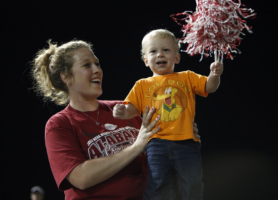 Lindsey Thompson, of Texas, and her son Tate, 20 months, celebrate during Game 3 of the Women's College World Series softball championship between OU and Alabama at ASA Hall of Fame Stadium in Oklahoma City, Wednesday, June 6, 2012.  Photo by Garett Fisbeck, The Oklahoman