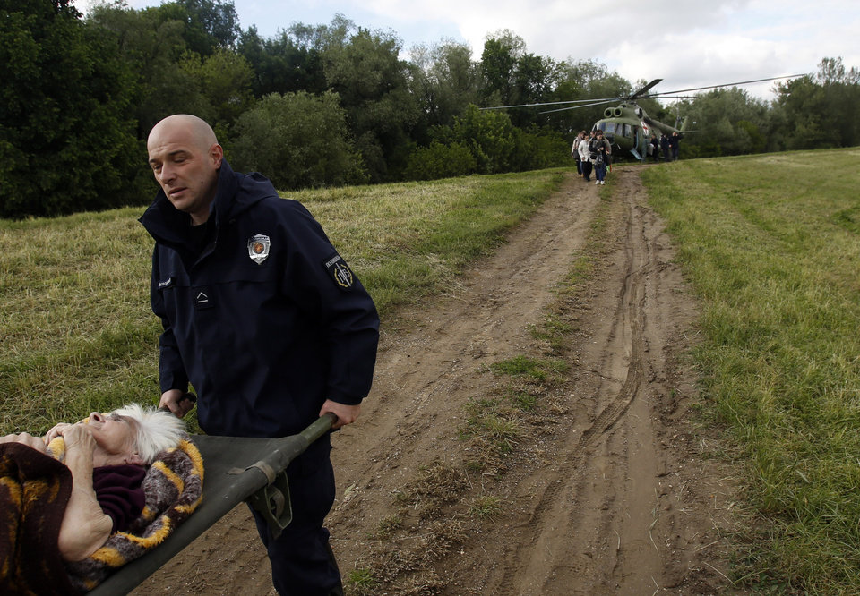 Photo - Serbian police officers carry an old woman out of military helicopter during flood evacuation from Obrenovac, some 30 kilometers (18 miles) southwest of Belgrade Serbia, Saturday, May 17, 2014. Record flooding in the Balkans leaves at least 20 people dead in Serbia and Bosnia and is forcing tens of thousands to flee their homes. Meteorologists say the flooding is the worst since records began 120 years ago. (AP Photo/Darko Vojinovic)