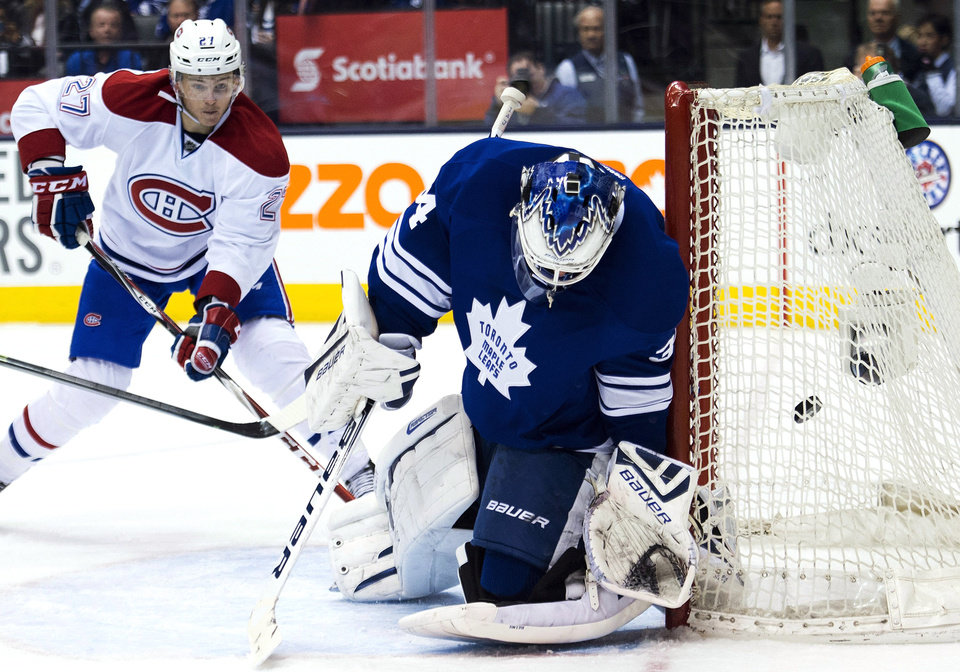 Photo - Toronto Maple Leafs goalie James Reimer, right, gets scored on by Montreal Canadiens' Tomas Plekanec, not shown, as Canadiens forward Alex Galchenyuk, left, looks on during the third period of an NHL hockey game in Toronto on Saturday, March 22, 2014.  (AP Photo/The Canadian Press, Nathan Denette)