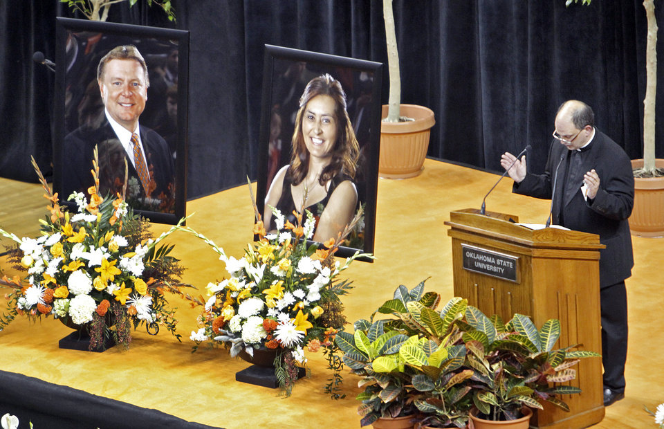 Photo - Father Kenneth Harder says a prayer during the memorial service for Oklahoma State head basketball coach Kurt Budke and assistant coach Miranda Serna at Gallagher-Iba Arena on Monday, Nov. 21, 2011 in Stillwater, Okla. The two were killed in a plane crash along with former state senator Olin Branstetter and his wife Paula while on a recruiting trip in central Arkansas last Thursday. Photo by Chris Landsberger, The Oklahoman
