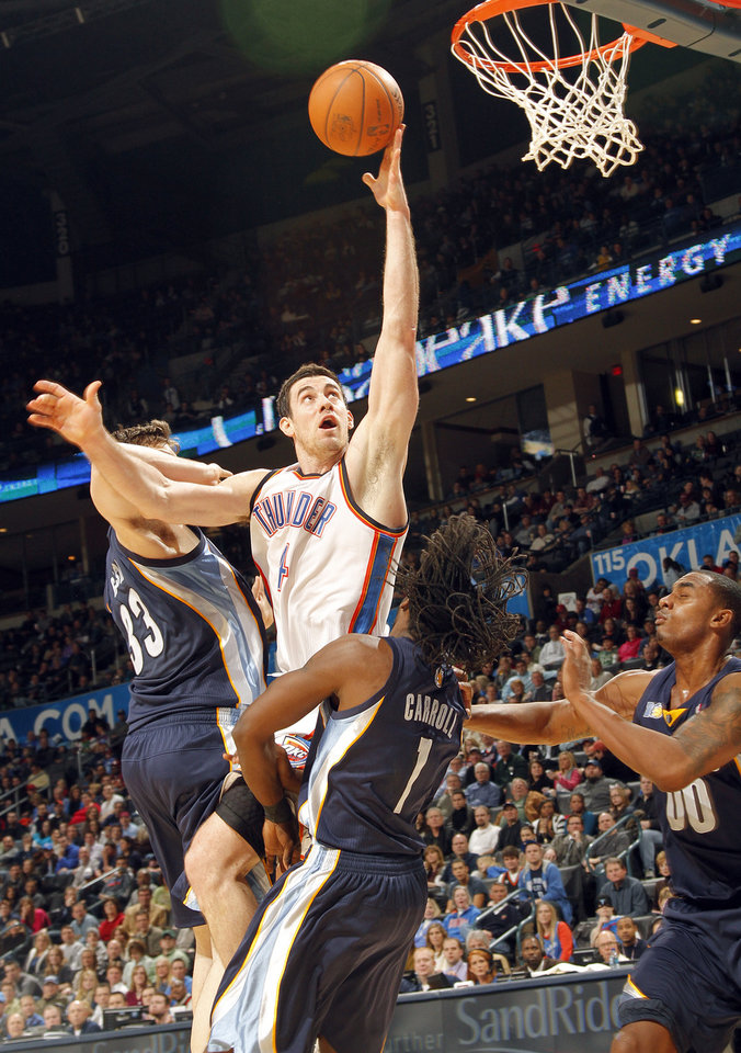 Photo - The Thunder's Nick Collison (4) drives to the basket past Memphis' Marc Gasol (33) and DeMarre Carroll (1) during the NBA basketball game between the Oklahoma City Thunder and the Memphis Grizzlies at the Oklahoma City Arena on Tuesday, Feb. 8, 2011, Oklahoma City, Okla.Photo by Chris Landsberger, The Oklahoman