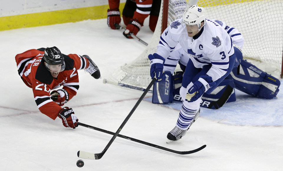 Photo - New Jersey Devils' Ryan Carter (20) dives for the puck with Toronto Maple Leafs' Dion Phaneuf (3) during the second period of an NHL hockey game, Sunday, March 23, 2014, in Newark, N.J. (AP Photo/Mel Evans)