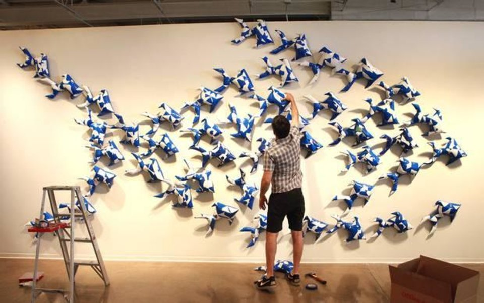 """Photo -  Dallas-based artist Jason Willaford installs vinyl fish he crafted from a reclaimed billboard into an installation titled """"In Business for Small Business"""" at Oklahoma Contemporary Arts Center. The installation is part of his exhibit """"Vinyl Exposed"""" at the gallery. Photos by David McDaniel, The Oklahoman"""