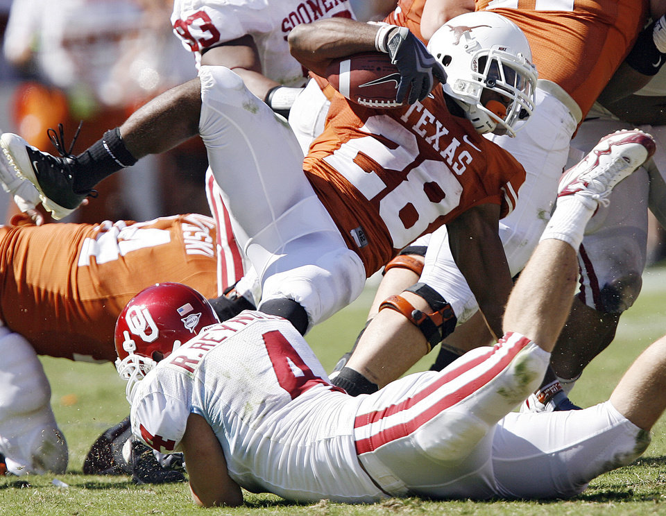 Photo - Oklahoma's Ryan Reynolds (4) trips up Texas' Fozzy Whittaker (28) during the Red River Rivalry college football game between the University of Oklahoma Sooners (OU) and the University of Texas Longhorns (UT) at the Cotton Bowl in Dallas, Texas, Saturday, Oct. 17, 2009. Photo by Chris Landsberger, The Oklahoman