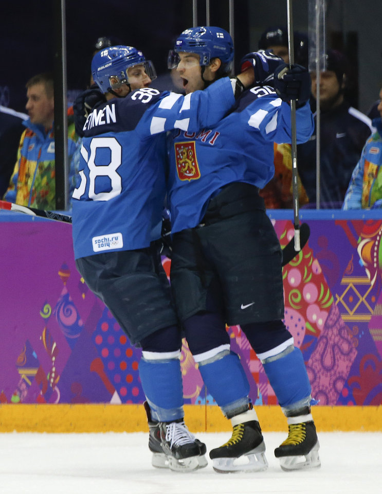 Photo - Finland defenseman Juuso Hietanen celebrates with forward Juhamatti Aaltonen after Aaltonen scored a goal against Russia in the first period of a men's quarterfinal ice hockey game at the 2014 Winter Olympics, Wednesday, Feb. 19, 2014, in Sochi, Russia. (AP Photo/Julio Cortez)