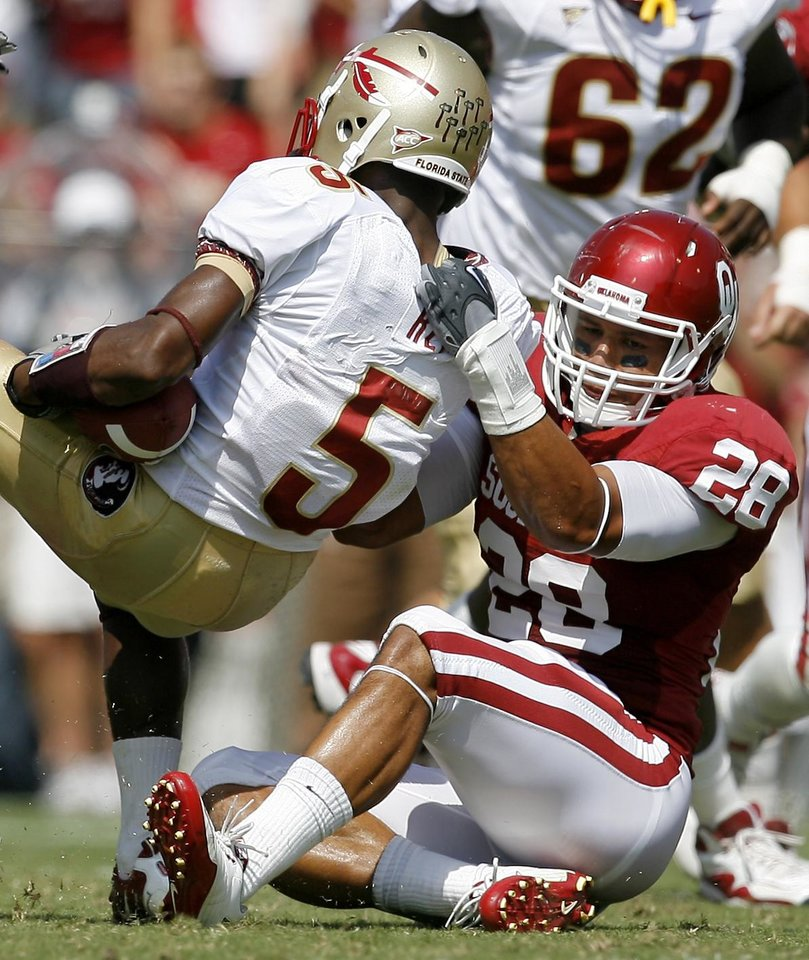 Photo - OU's Travis Lewis brings down Greg Reid of Florida State during the first half of the college football game between the University of Oklahoma Sooners (OU) and Florida State University Seminoles (FSU) at the Gaylord Family-Oklahoma Memorial Stadium on Saturday, Sept. 11, 2010, in Norman, Okla.   Photo by Bryan Terry, The Oklahoman