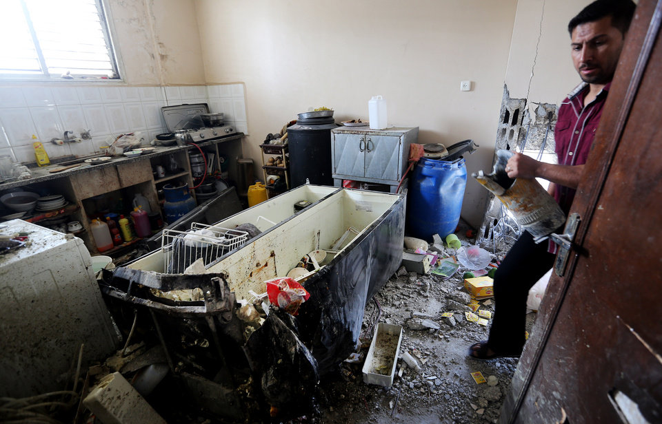 Photo - Palestinian inspects a ruble of a destroyed house of Qasim Alwan, 4, Imad Alwan, 6, after it was hit by an Israeli tank shell on Friday in Gaza City, Saturday, July 19, 2014. The brothers were killed along with one year-old Rizk Hayek, who lived nearby, and was hit by shrapnel. (AP Photo/Hatem Moussa)