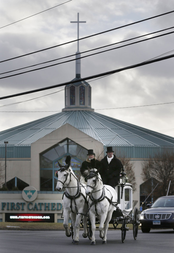 Photo - A horse drawn carriage carrying the body of Anna Grace Marquez-Greene leaves the church after her funeral in Bloomfield, Conn., Saturday, Dec. 22, 2012.  Marquez-Greene, 6,  was killed when gunman Adam Lanza opened fire at Sandy Hook Elementary School last week, killing 26 people, including 20 children, before killing himself. (AP Photo/Seth Wenig) ORG XMIT: CTSW110