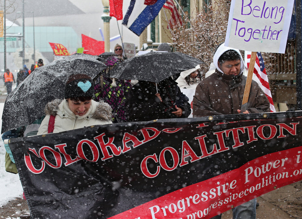 Photo - Protesters brave the cold and snow as they march from the Capitol to a park in Denver on Wednesday, May 1, 2013. About 200 people gathered at the Capitol for immigration reform. The May Day rallies carry a special sense of urgency this year, two weeks after a bipartisan group of senators introduced a bill that would bring many of the estimated 11 million living in the U.S. illegally out of the shadows.  Colorado's rally comes just after the governor signed a bill allowing students in the country illegally to pay in-state tuition at state colleges and universities, ending a 10-year political battle.(AP Photo/Ed Andrieski)