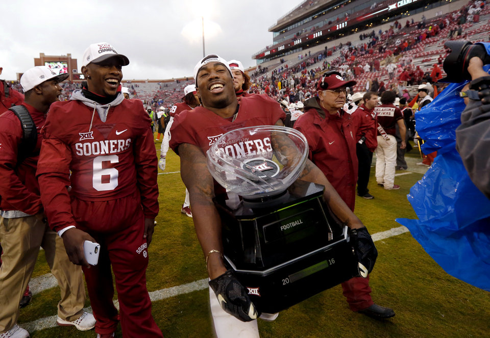 Photo - Oklahoma's Ahmad Thomas (13) carries the Big 12 trophy after the Bedlam college football game between the Oklahoma Sooners (OU) and the Oklahoma State Cowboys (OSU) at Gaylord Family - Oklahoma Memorial Stadium in Norman, Okla., Saturday, Dec. 3, 2016. Oklahoma won 38-20. Photo by Bryan Terry, The Oklahoman