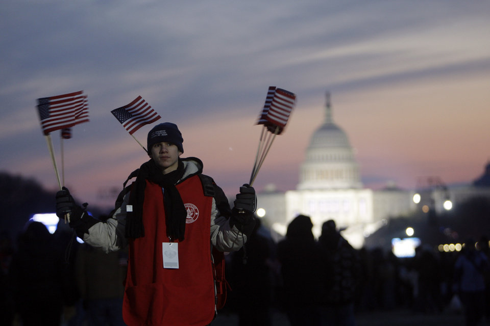 Photo - A Boy Scout is ready to hand out flags on the National Mall in view of the the U.S. Capitol in Washington, Tuesday, Jan. 20, 2009, before the swearing-in ceremony of President-elect Barack Obama. (AP Photo/Matt Rourke)