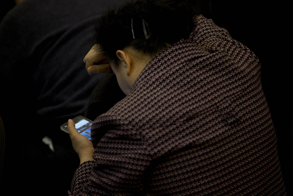 Photo - A relative of Chinese passengers aboard the missing Malaysia Airlines Flight MH370 uses her smartphone to watch a news conference held by the airlines' officials at a hotel ballroom in Beijing Monday, March 17, 2014. The search for the missing Malaysian jet pushed deep into the northern and southern hemispheres Monday as Australia took the lead in scouring the seas of the southern Indian Ocean and Kazakhstan - about 10,000 miles to the northwest - answered Malaysia's call for help in the unprecedented hunt. (AP Photo/Andy Wong)