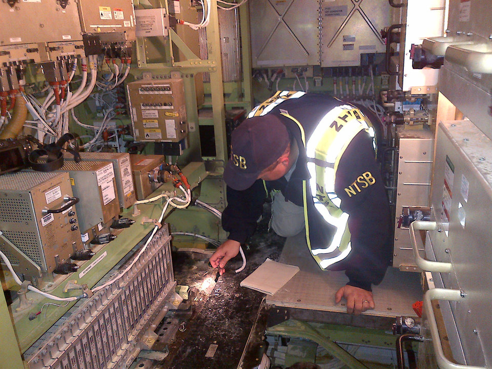 Photo - In this image released by the National Transportation Safety Board and released Jan. 11, 2013, NTSB Investigator Mike Bauer works inside the Boeing 787