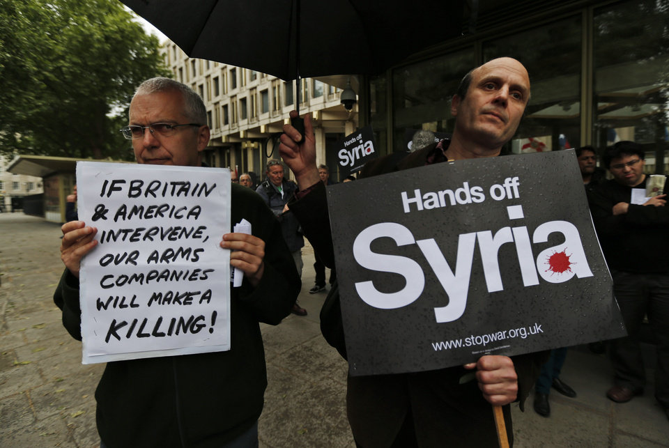 Photo - Protesters hold placards as they demonstrate against western intervention in Syria, outside the US embassy in central London, Saturday, June 15, 2013. (AP Photo/Lefteris Pitarakis)