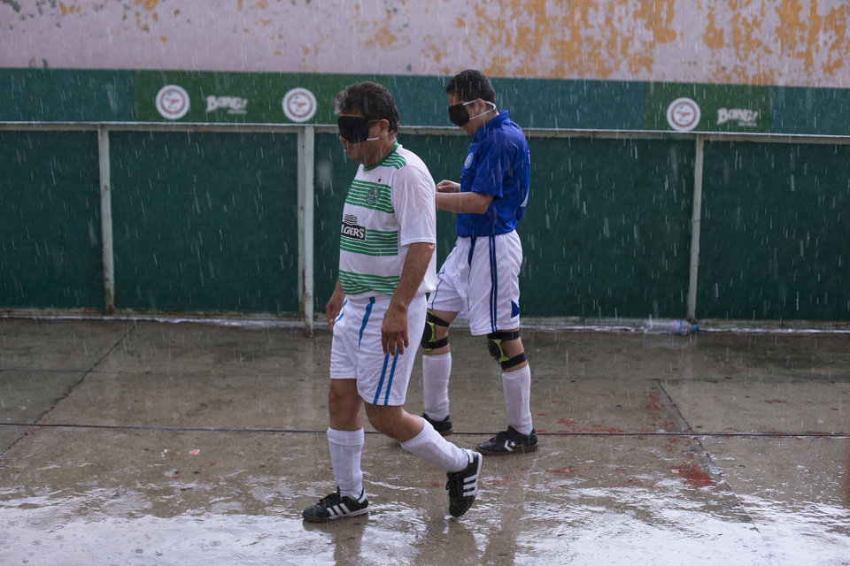 """Photo - In this Sunday, June 8, 2014 photo, players leave the court after a downpour interrupted a mixed-team match following the league final, in Mexico City. """"For us, this is important because we have almost no recreational spaces,"""