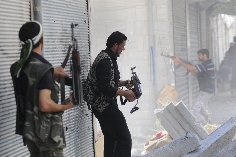 Photo -   In this Wednesday, Aug. 1, 2012 photo, a Free Syrian Army soldier fires his weapon during clashes with Syrian government forces in Saladin neighborhood, in Aleppo, Syria. (AP Photo/Alberto Prieto)