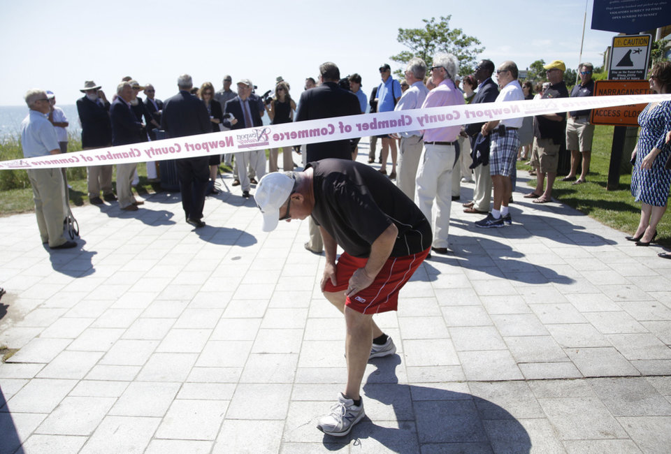 Photo - A walker cuts under the ceremonial ribbon as state and local officials hold a ribbon cutting ceremony to officially reopening the Cliff Walk Tuesday, June 24, 2014 in Newport, RI. Parts of the well known attraction were damaged by Superstorm Sandy in 2012.  (AP Photo Stephan Savoia)