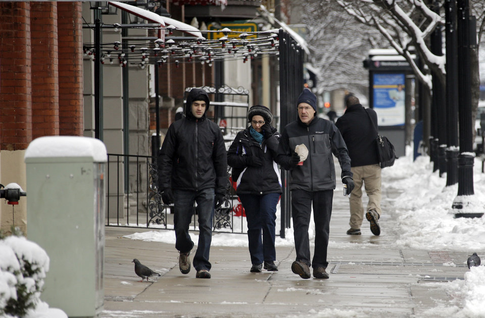 Pedestrians walk down St. Clair Ave. in downtown Cleveland Thursday, Dec. 27, 2012. Ohioans picked their way around snow and slush left from the winter's biggest storm so far, with one major interstate still closed for commuters after an evening accident. (AP Photo/Mark Duncan)