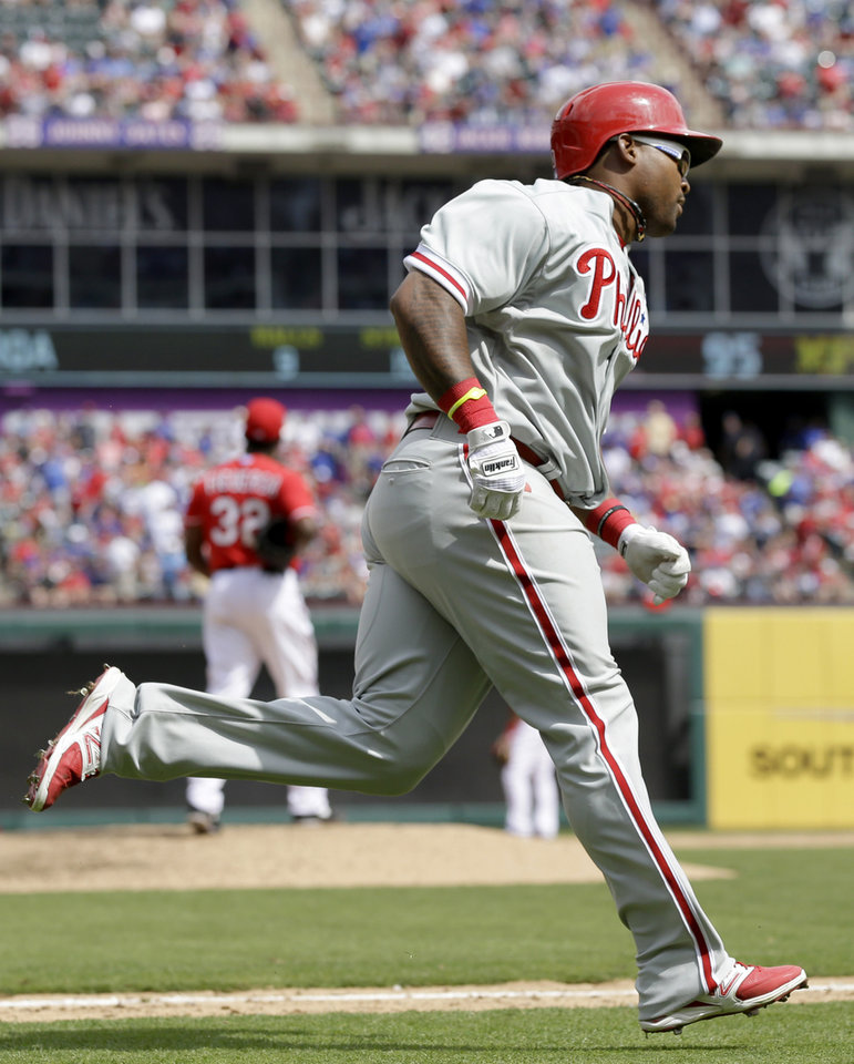 Photo - Philadelphia Phillies' Marlon Byrd rounds the bases after hitting a home run off Texas Rangers relief pitcher Pedro Figueroa during the sixth inning of an opening day baseball game at Globe Life Park, Monday, March 31, 2014, in Arlington, Texas.  (AP Photo/Tony Gutierrez)