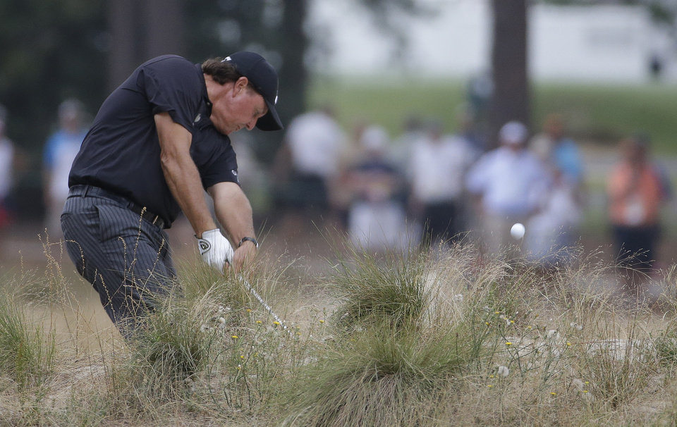 Photo - Phil Mickelson hits out of the native area on the fifth hole during the first round of the U.S. Open golf tournament in Pinehurst, N.C., Thursday, June 12, 2014. (AP Photo/David Goldman)