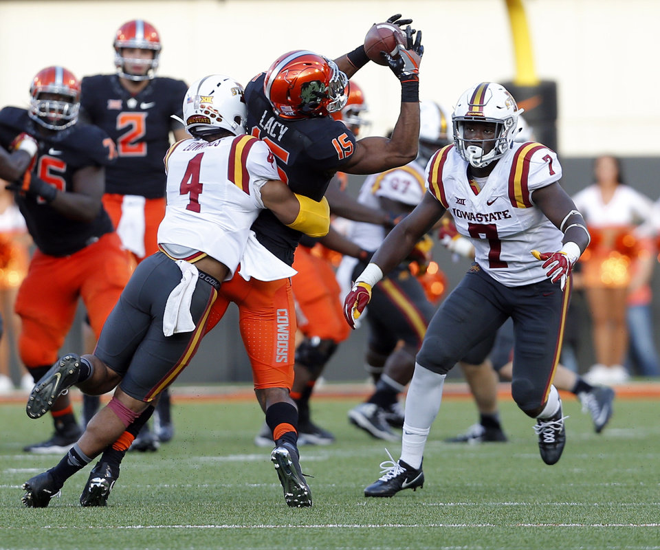 Photo - Oklahoma State's Chris Lacy (15) makes a catch in between Iowa State's Evrett Edwards (4) and Willie Harvey (7) in the fourth quarter during a college football game between the Oklahoma State University Cowboys (OSU) and the Iowa State University at Boone Pickens Stadium in Stillwater, Okla., Saturday, Oct. 8, 2016. Photo by Sarah Phipps, The Oklahoman