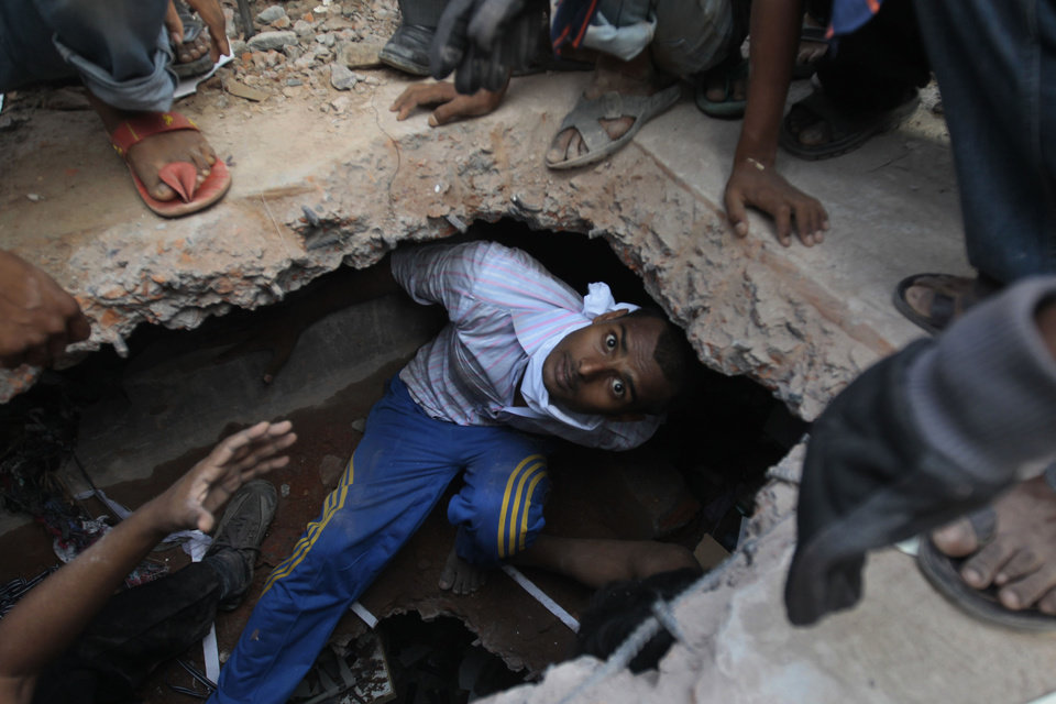 Photo - A Bangladeshi rescuer looking for survivors emerges from beneath a concrete slab of a building that collapsed Wednesday in Savar, near Dhaka, Bangladesh,Thursday, April 25, 2013. By Thursday, the death toll reached at least 194 people as rescuers continued to search for injured and missing, after a huge section of an eight-story building that housed several garment factories splintered into a pile of concrete on Wednesday. (AP Photo/A.M.Ahad)