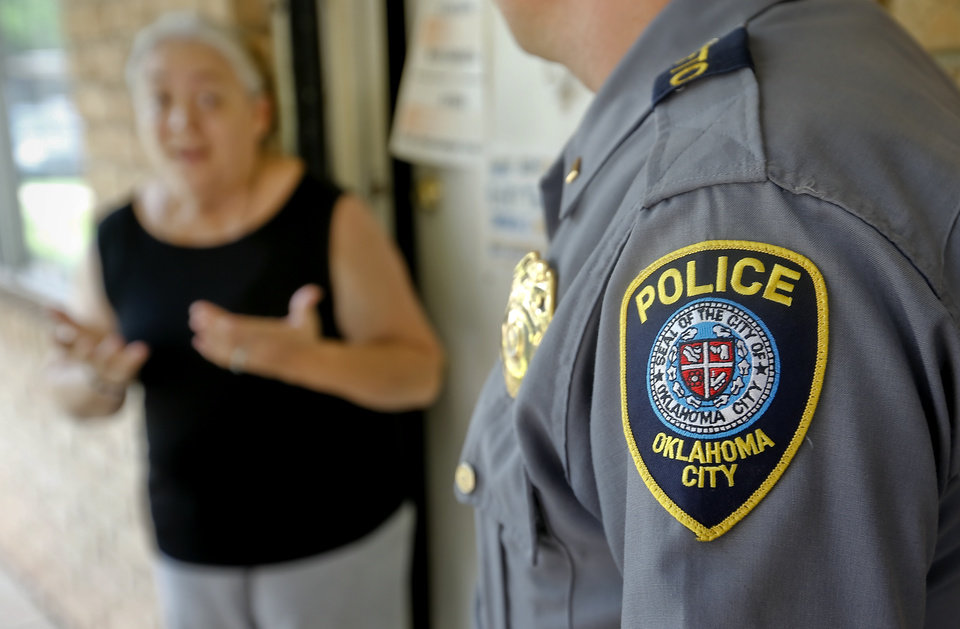 Photo -  The Hefner Patrol Division's Isaac Goodman talks to resident Kat Delgado on Tuesday at the Windsor Village Apartments in Oklahoma City. The division has been on a yearlong initiative to cut back the violence around the area in northwest Oklahoma City. Photos by Chris Landsberger, The Oklahoman       -