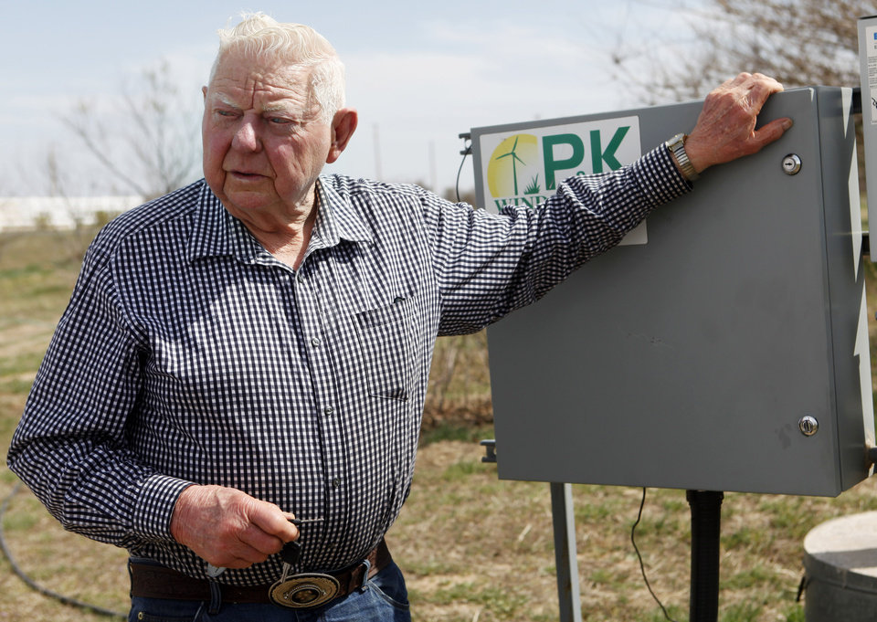 Photo -  Herb Hill opens the control unit of his 100-foot-tall wind turbine which generates electricity for his home near Crescent. Photo by KT King, The Oklahoman    KT King -
