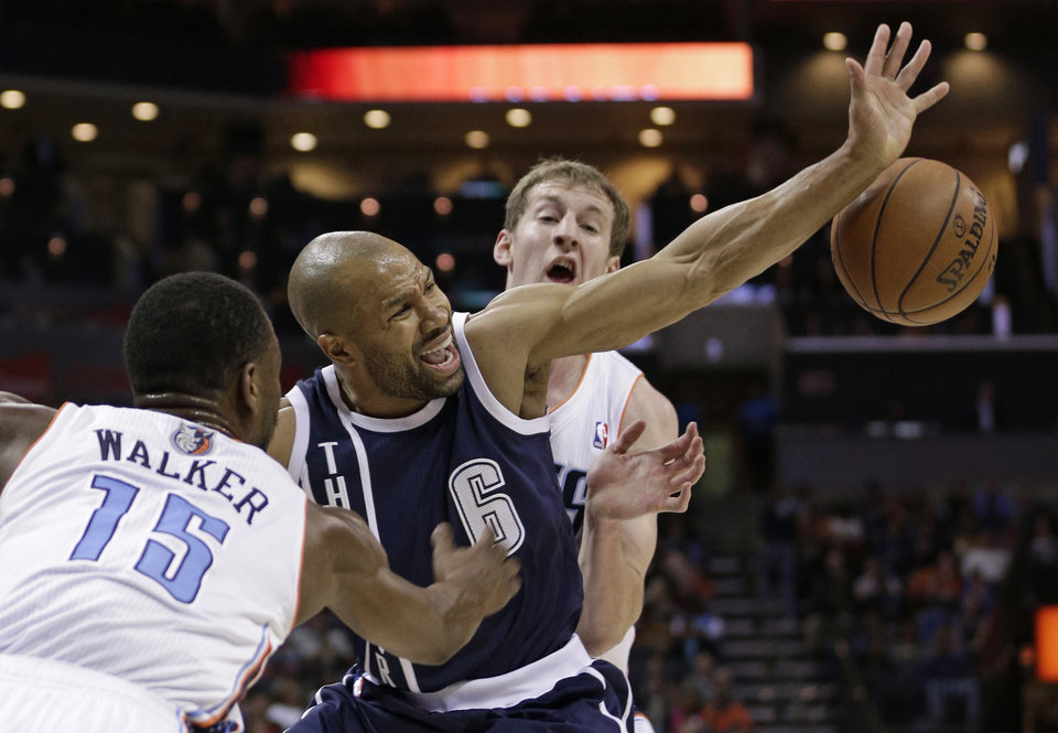 Oklahoma City Thunder's Derek Fisher, center, loses the ball as he is trapped by Charlotte Bobcats' Kemba Walker, front, and Cody Zeller during the second half of an NBA basketball game in Charlotte, N.C., Friday, Dec. 27, 2013. The Thunder won 89-85. (AP Photo/Chuck Burton)