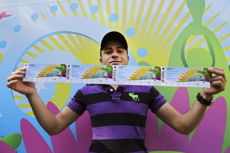 Photo - Colombia soccer fan John Gomes shows his newly bought tickets for Colombia's World Cup soccer games outside a ticket center at Ibirapuera Gym in Sao Paulo, Brazil, Wednesday, June 4, 2014. Tickets for the World Cup opener were sold out fast, as fans lined up in the cold to try to buy what was left for the other matches. (AP Photo/Nelson Antoine)
