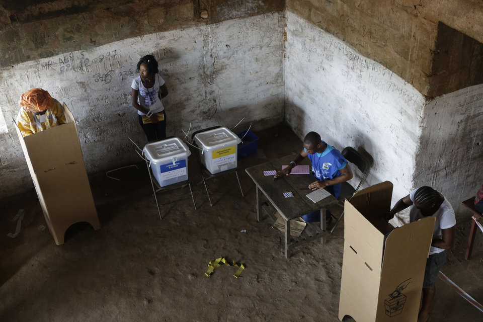 Voters fill out their ballots behind privacy screens as poll workers oversee the process, at a polling station in Freetown, Sierra Leone, Saturday, Nov. 17, 2012. A decade after Sierra Leone's brutal civil war, voters on Saturday chose between an incumbent president who has provided new roads and free health care and a field of opposition candidates who decry the poverty and pace of economic recovery. (AP Photo/Rebecca Blackwell)