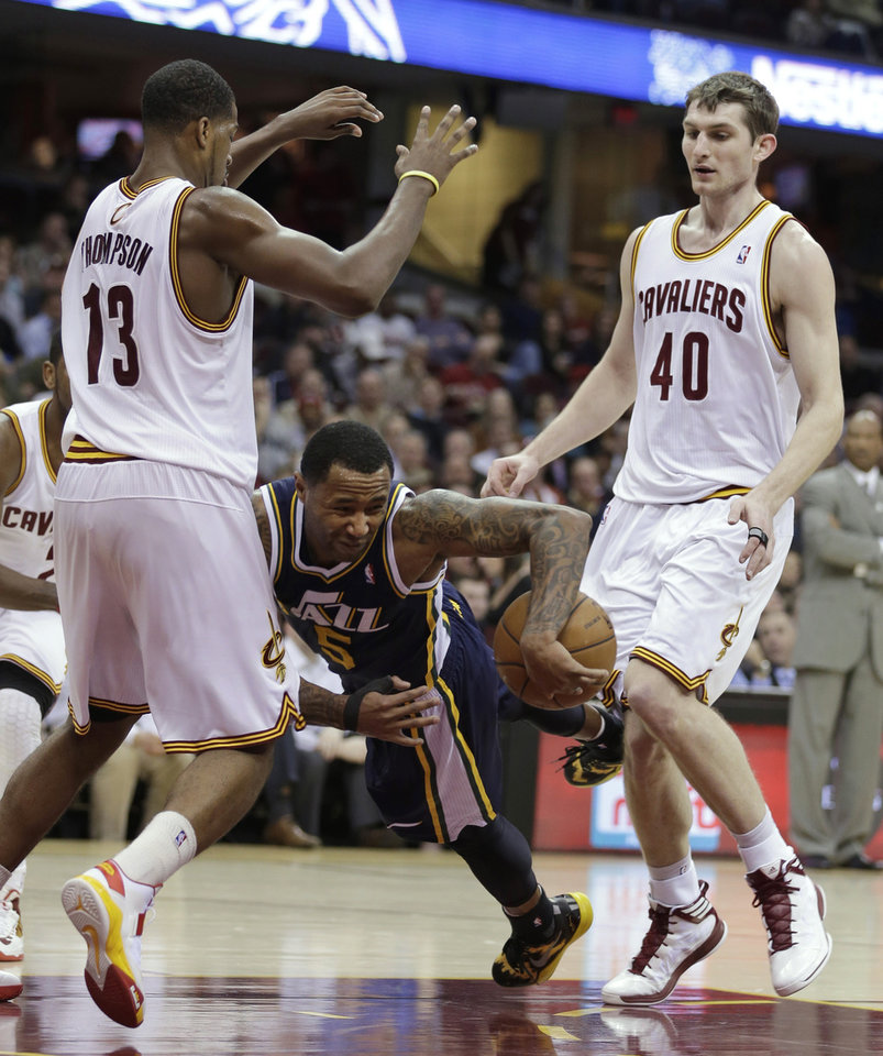 Utah Jazz's Mo Williams, center, trips as he tries to pass between  Cleveland Cavaliers' Tristan Thompson, left, and Tyler Zeller during the second quarter of an NBA basketball game Wednesday, March 6, 2013, in Cleveland. (AP Photo/Tony Dejak)