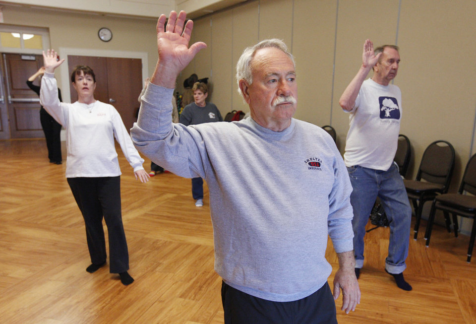 Photo - Jim Bryan, of Edmond, center, participates in a tai chi class at Edmond Senior Center. Classes are on Mondays and Fridays.