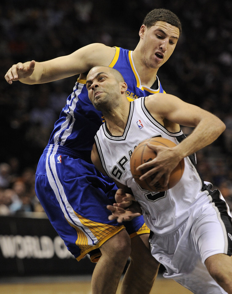 Photo - San Antonio Spurs guard Tony Parker, right, of France, drives around Golden State Warriors guard Klay Thompson during the first half of an NBA basketball game on Wednesday, April 2, 2014, in San Antonio. (AP Photo/Darren Abate)